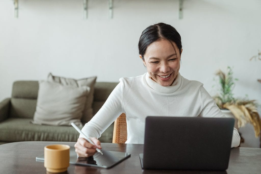 A woman sits at a stylish modern table watching a life science webinar, taking notes and engaged